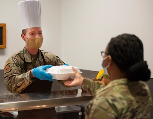 Chief Master Sgt. Troie A. Croft, Air Force Life Cycle Management Center command chief, hands an Airman a Thanksgiving dinner