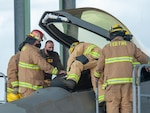 Lt. Col. Steven Augugliaro, 154th Wing F-22 flight safety officer, works with members of the Federal Fire Department during a pilot extraction exercise Nov. 20, 2020, at Joint Base Pearl Harbor-Hickam, Hawaii.