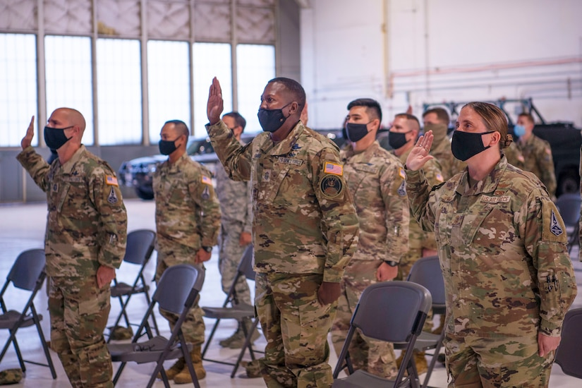 Service members raise hands to swear oaths in hangar.