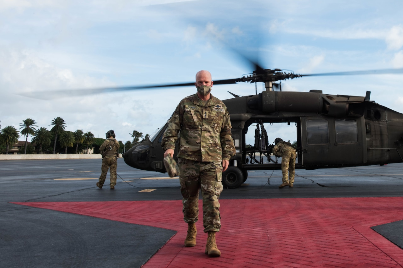 A man walks away from a helicopter.