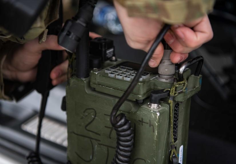 Close up of hand putting plug into radio.