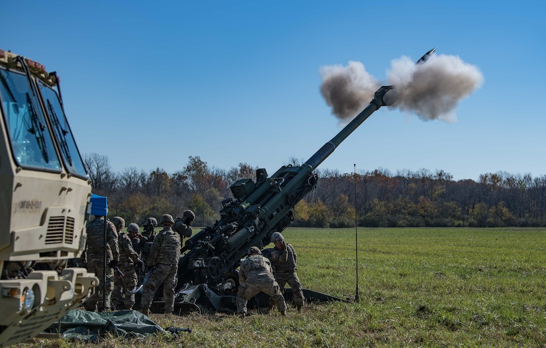 A piece of artillery fires in a field.