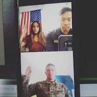 Phone screen showing a man administering the Oath of Enlistment to a lady virtually