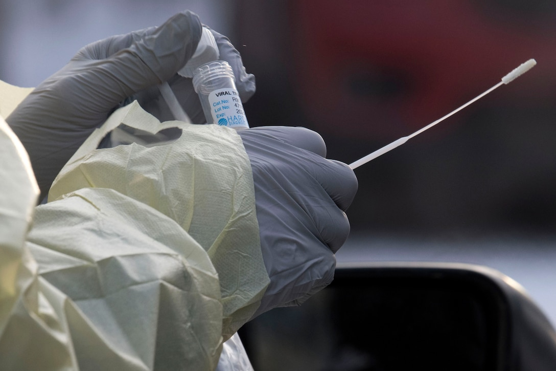 Two gloved hands hold a vial and swab.