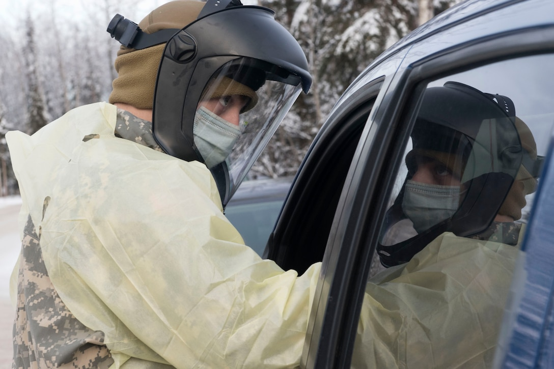 A soldier gives a COVID-19 test to someone in a car.