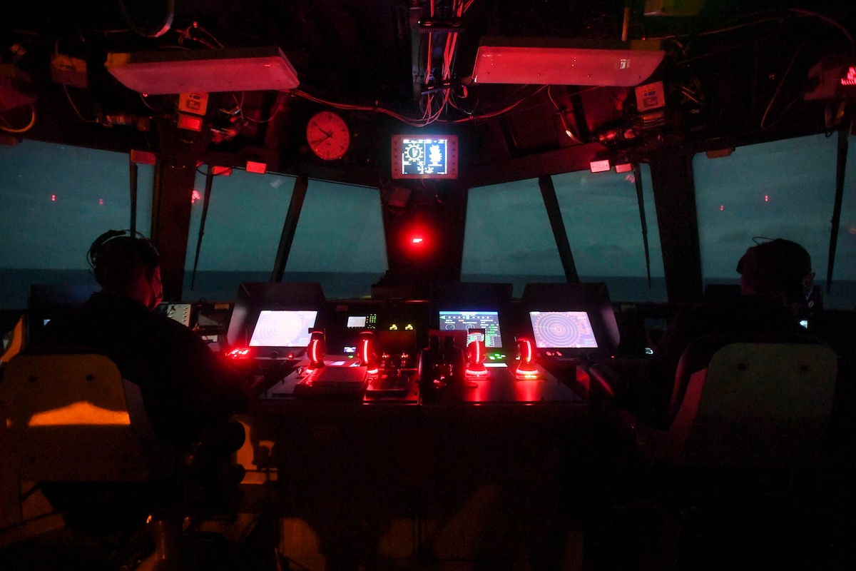 Two sailors sit in the navigation bridge of a ship illuminated by monitors and red light at night.