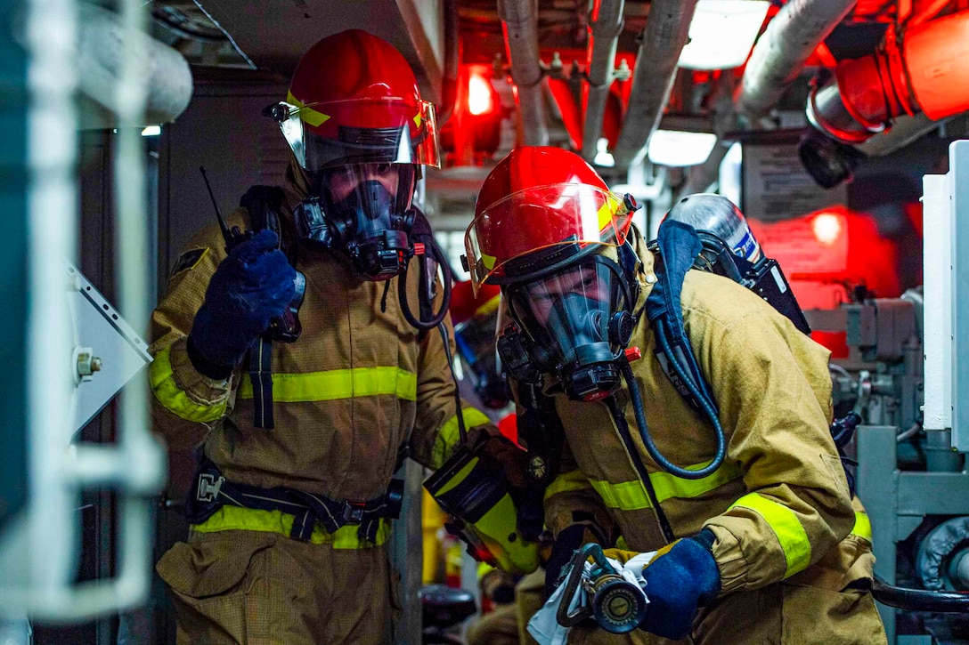 Two sailors wearing fire protective gear stand side-by-side; one holding a communication device and the other holding a water hose.