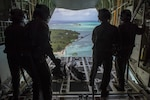 Loadmasters with the 36th Airlift Squadron out of Yokota Air Base, Japan, watch as the four 