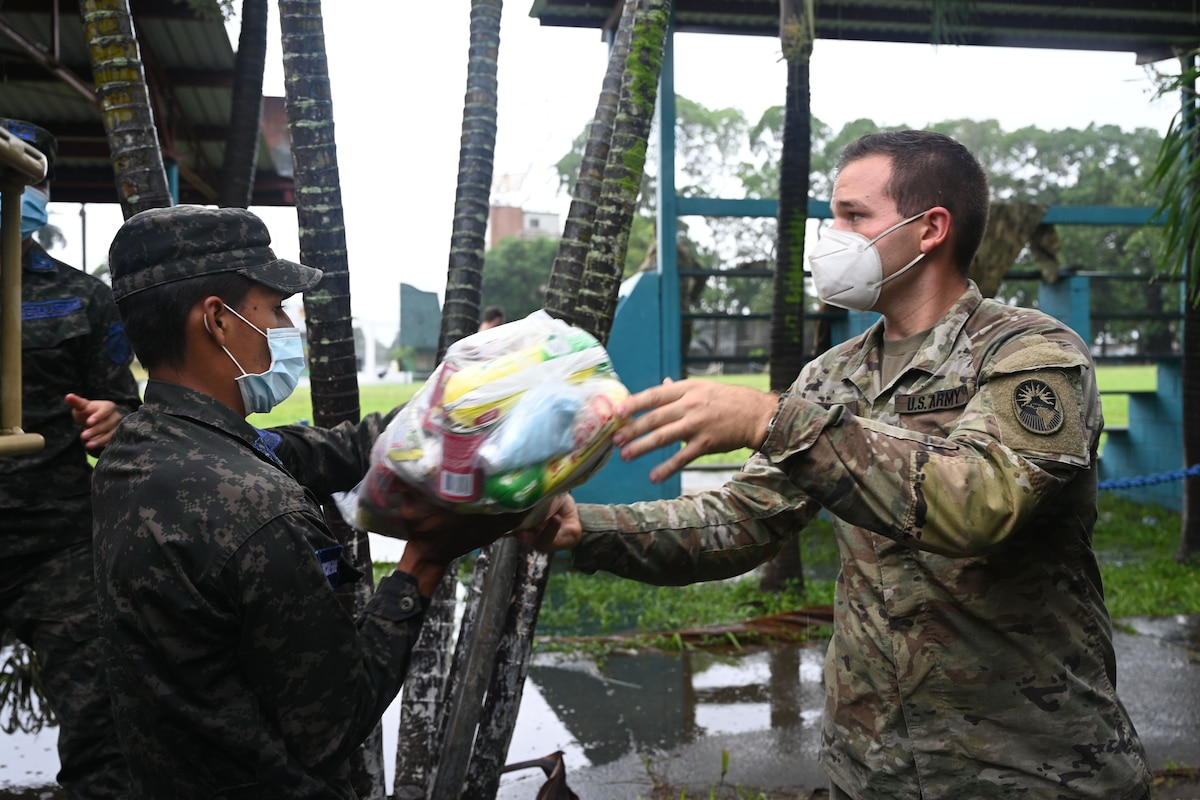 A soldier passes a bundle of food to an airman.