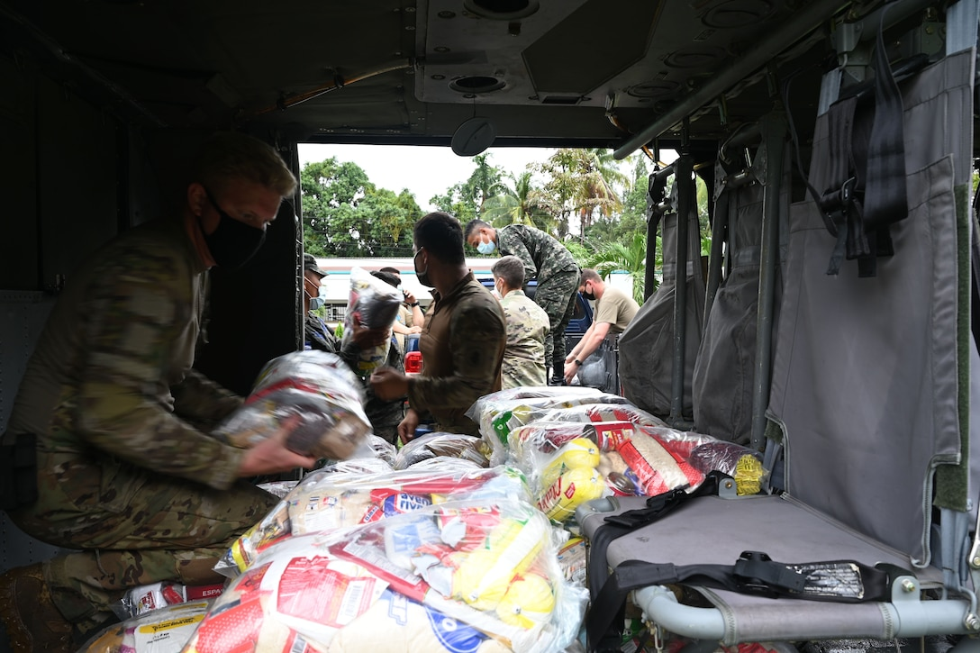 A soldier kneeling in a vehicle organizes bundles of food.