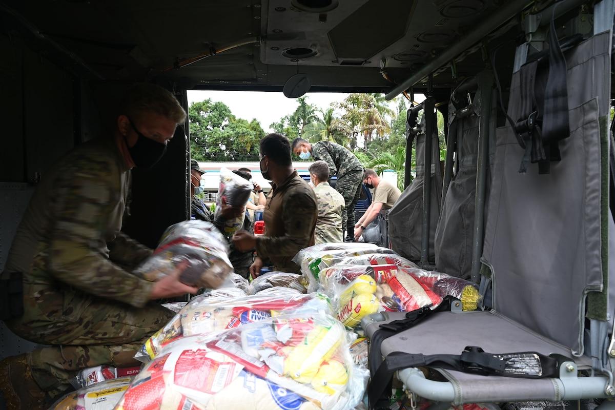 A soldier kneeling in a vehicle organizes bundles of food.
