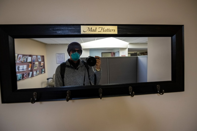 A man takes a picture of himself in a mirror in a medical center.