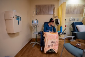A man sits in a chair with tubes connected to his body while he receives chemotherapy.