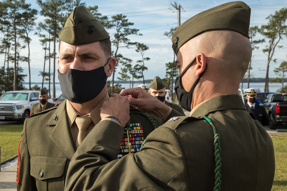 A Marine puts a braided cord on the shoulder of another Marine.