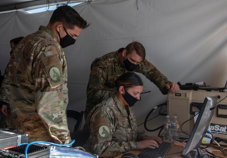 Three airmen study a computer under a tent.