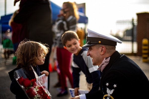 Command Master Chief Anthony Amato, the chief of the boat assigned to the Virginia-class fast-attack submarine USS John Warner (SSN 785), greets his sons during the boat's homecoming.