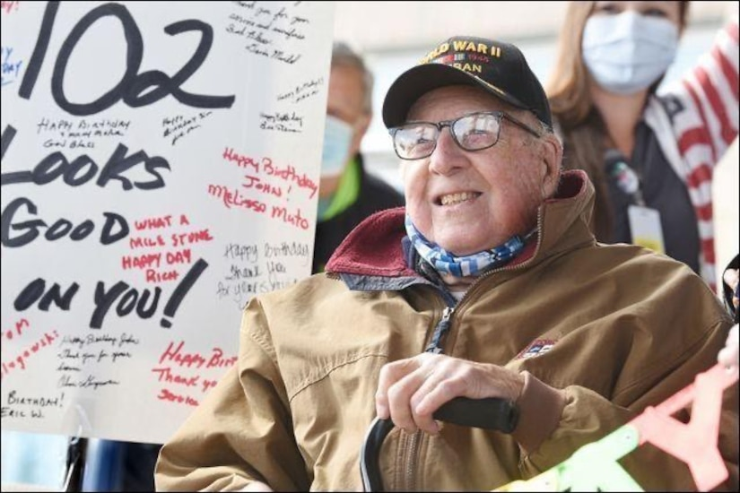 A military veteran is surrounded by people and signs.