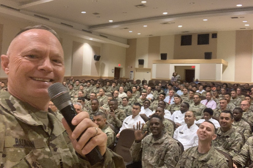 A soldier takes a picture of himself and an audience.