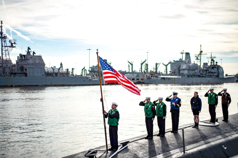 Sailors standing in formation on top of a submarine salute as one holds the American flag.