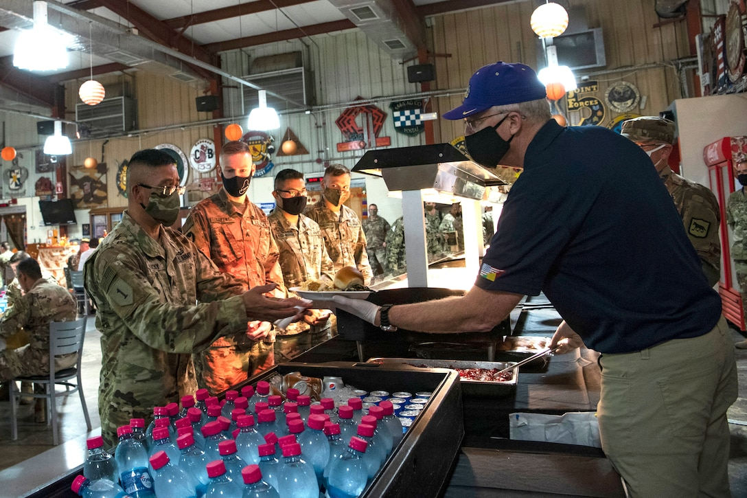 Acting Defense Secretary Christopher C. Miller serves Thanksgiving dinner to troops.