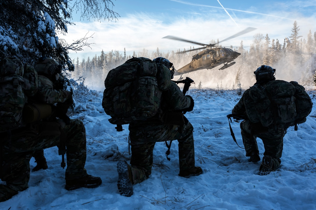 Three airmen kneel in the snow watching a helicopter land.