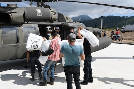 U.S. Army Soldiers and Honduran volunteers load humanitarian aid on to a UH-60 Black Hawk helicopter at a coffee processing facility in Belen Gualcho, Ocotepeque, Honduras.