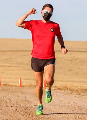 Maj. Jason Brosseau, 26th Space Aggressors Squadron, raises his fist as he approaches the finish line Nov. 20, 2020, at Schriever Air Force Base, Colorado during the 19th annual Turkey Trot race. Brosseau's finish marked his third consecutive victory in the event. (U.S. Space Force photo by Marcus Hill)