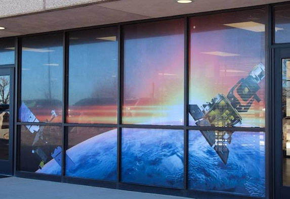 """Windows at the restricted area North Portal display satellites as part of the """"Life Series,"""" created by the 50th Mission Support Group at Schriever Air Force Base, Colorado. The series will include Air and Space Force-related photos to highlight Airmen who work within the RA. Photos displayed indoors will include squadrons such as the 50th Security Forces Squadron, 50th Civil Engineer Squadron, the dining facility and more. Images displayed on windows will be completed when weather permits.  (U.S. Space Force photo by Marcus Hill)"""
