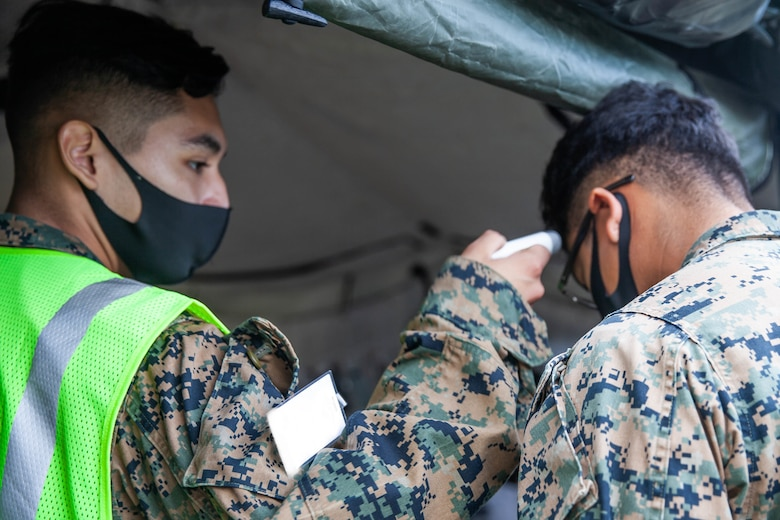 U.S. Marines with 1st Marine Aircraft Wing (MAW), perform COVID-19 prevention measures during Exercise Driven Thermite 21 at Marine Corps Air Station Futenma, Okinawa, Japan, Nov. 19, 2020. This exercise ensures that 1st MAW personnel are ready to plan and execute air operations in the Indo-Pacific by operating in a simulated environment. (U.S. Marine Corps photo by SSgt. Ronald Spotswood)