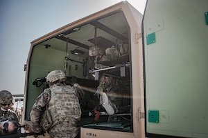 U.S. soldiers lift a litter into an emergency transport vehicle