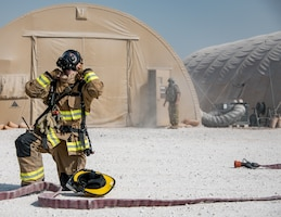 a firefighter dons a mask before entering a building full of simulated smoke from a machine