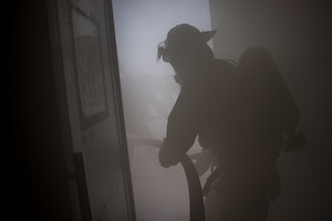 firefighter pulls a hose into a building full of smoke from a smoke machine