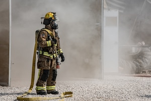 firefighter stands with hose over shoulder with haze of smoke behind him
