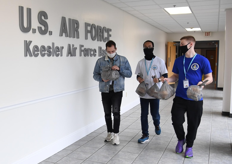 U.S. Air Force Airman 1st Class Hunter Shores and Airman Khoa Nguyen, 335th Training Squadron students, and Airman Austin Lemke, 338th Training Squadron student, carry bags of cookies inside the Levitow Training Support Facility at Keesler Air Force Base, Mississippi, Nov. 26, 2020. Due to the concern over rising COVID-19 cases, 81st TRG students weren't allowed to leave Keesler for the holidays. Keesler personnel were asked to donate cookies to the students to increase moral. (U.S. Air Force photo by Kemberly Groue)