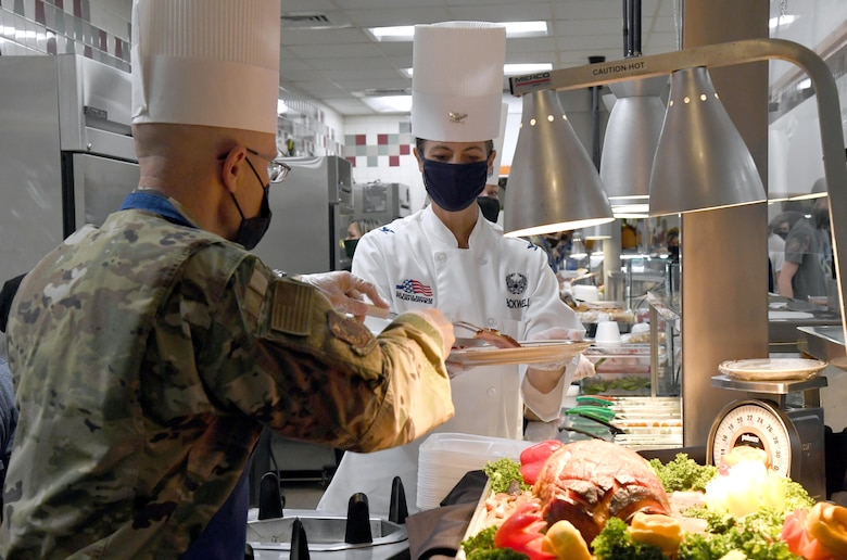 U.S. Air Force Col. Chance Geray, 81st Training Group commander, places a piece of ham on a plate for Col. Heather Blackwell, 81st Training Wing commander, inside the Azalea Dining Facility at Keesler Air Force Base, Mississippi, Nov. 26, 2020. It is tradition at Keesler for commanders, first sergeants and superintendents to serve a Thanksgiving meal at the dining facility to technical training and permanent party Airmen who are not able to go home for the holiday. (U.S. Air Force photo by Kemberly Groue)