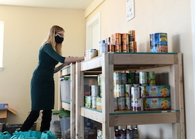 Rachel Crist, Buckley Spouses' Group treasurer, packs a bag with food before the grand opening of Gretel's Food Pantry on Buckley Air Force Base, Colo., Nov. 25, 2020. A survey that returned over 120 responses revealed the critical need for food assistance on Buckley. (U.S. Space Force photo by Airman 1st Class Haley N. Blevins)