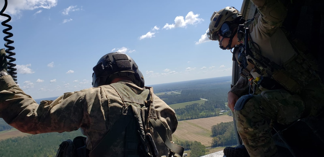 Two men look out onto farmland from an open helicopter door.