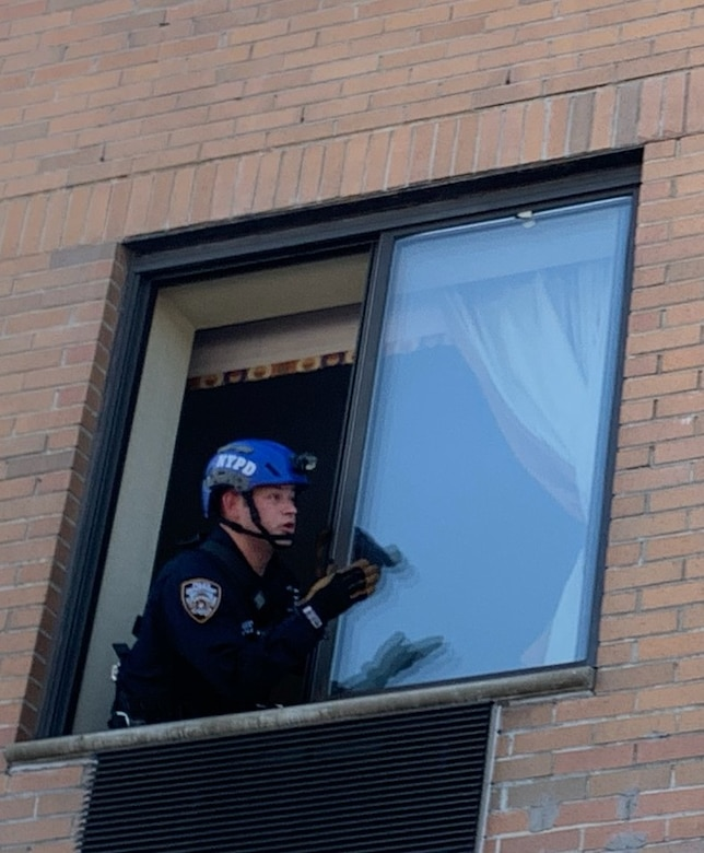 A man in an NYPD helmet talks to someone through an open window.