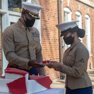 The oldest Marine in attendance, hands the youngest Marine in attendance a piece of cake.