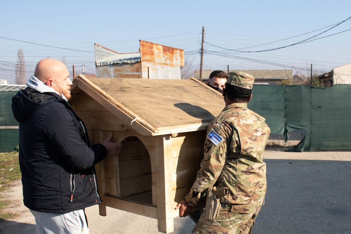 A service member and a civilian carry a doghouse.