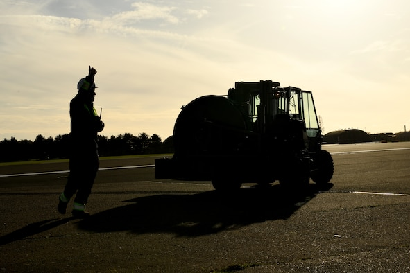 An Airman assigned to the 48th Civil Engineer Squadron marshals a forklift carrying a new BAK-12 arresting system at Royal Air Force Lakenheath, England, Nov. 22, 2020. In the event of an in-flight emergency, the BAK-12 system provides an avenue for pilots to safely land and slow their aircraft.  (U.S. Air Force photo by Senior Airman Christopher S. Sparks)