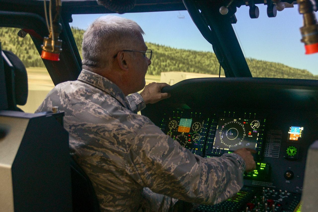 A man in a military uniform sits inside a simulated aircraft cockpit.