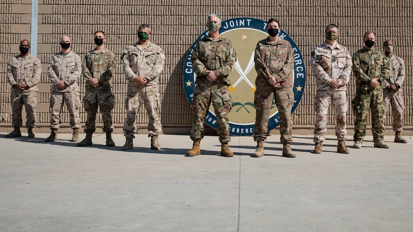 Service members from the Combined Joint Task Force - Operation Inherent Resolve Directorate of Military Assistance stand for a photo on Camp Arifjan, Kuwait, November 14, 2020. The DMA is a joint force initiative that supports the divestment of critical resources, training, and funding to vetted partner forces throughout the U.S. Army Central Command area of operations.