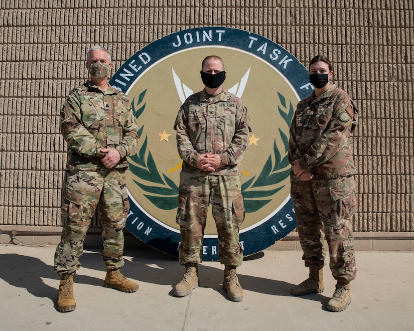 U.S. Army Col. John M. Dreska, U.S Counter-ISIS Train and Equip Fund (CTEF) program director at the 1st Theater Sustainment Command, operational command post stands between U.S. Army Lt. Col. Argot Carberry, (left) incoming director for the Combined Joint Task Force - Operation Inherent Resolve Directorate of Military Assistance and outgoing director U.S. Navy, Lt. Cmdr. Michelle Shaffstall (right) for a photo November 14, 2020 on Camp Arifjan, Kuwait. The DMA works with the 1st TSC to facilitate the divestment of critical assets to partner forces in the fight to defeat ISIS.