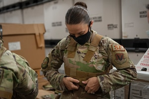 Photo of an Airman adjusting a vest