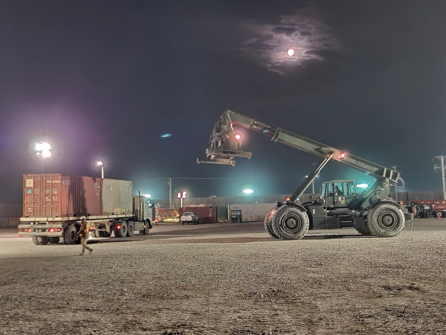 Defense Logistics Agency personnel take to the night to clear containers from a receiving and shipping point on Bagram Airfield, Afghanistan.