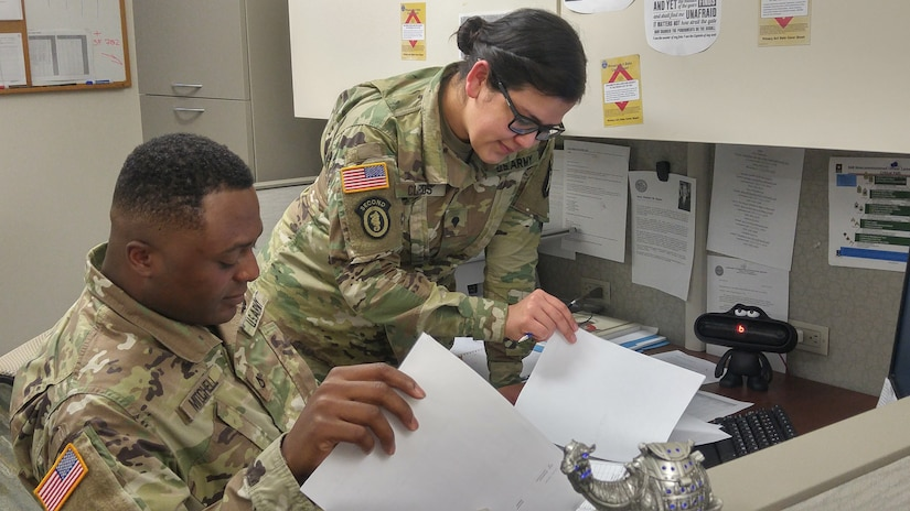 Pfc. Detron R. Mitchell, left, and Spc. Iris I. Claros, right, consolidate documents in the disbursing section of the Defense Military Pay Office for an inspection by the Network Audit Field Compliance Division of the Defense Finance and Accounting Service at Fort Campbell, Kentucky, Feb. 20, 2017. The U.S. Army Financial Management Command assumed the Army's military pay mission from the Defense Finance and Accounting Service on Oct. 1, 2020.  (U.S. Army photo by 1st Lt. Todd A. Kuzma)