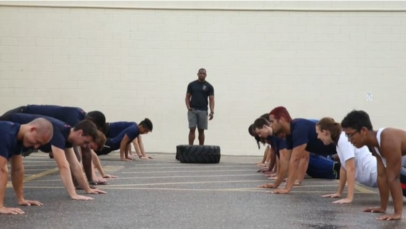 A man standing behind a tire on the ground watches several others around him do pushups.