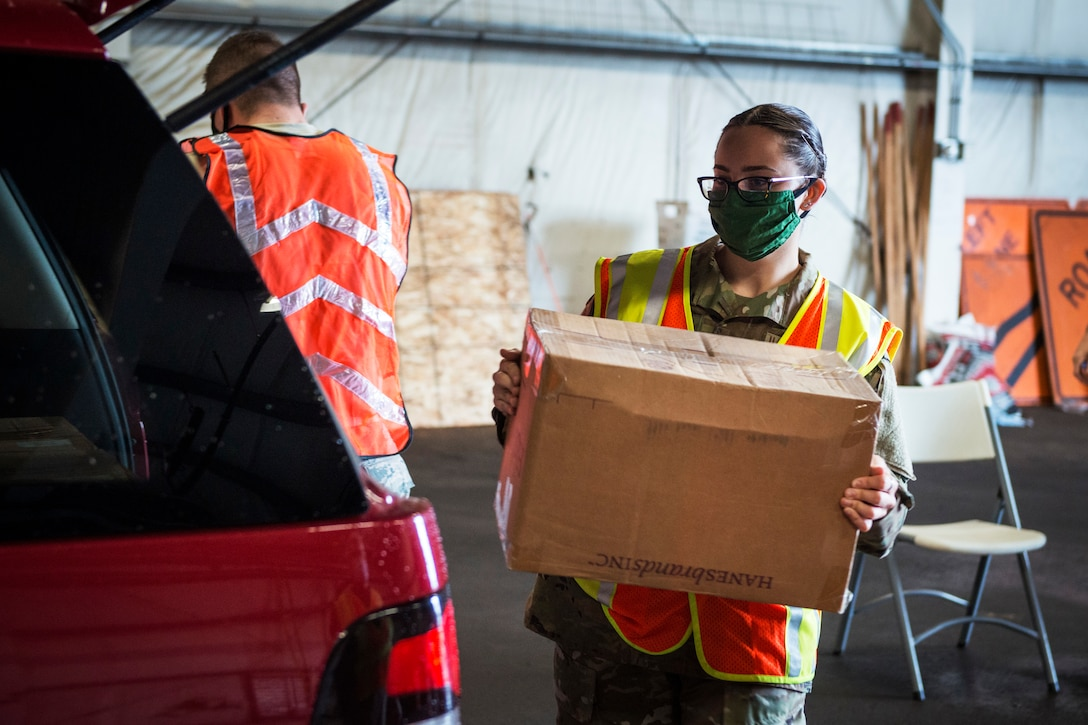 A female service member wearing a face mask and reflective vest carries a box to a vehicle.
