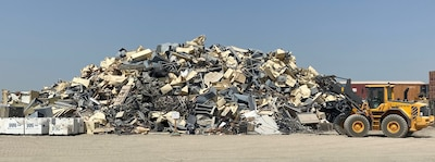 Material handlers gather scrap materials to prepare for removal operations to begin.